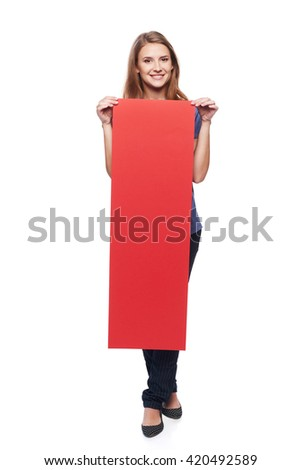 Full length young woman holding vertically red strip blank cardboard, over white background - stock photo