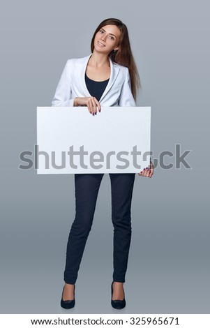 Full length young woman holding white blank cardboard, over gray background. - stock photo