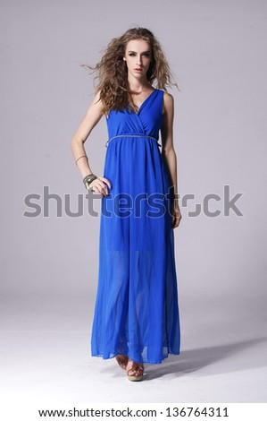 Full length young woman in blue dress posing in studio - stock photo