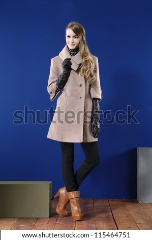 Full length young woman in coat posing with cube on wooden floor