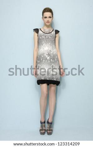 Full length young woman in elegant dress posing - stock photo