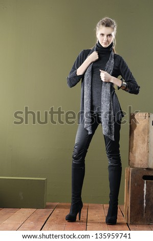 Full length young woman posing near chair with cube on wooden floor - stock photo