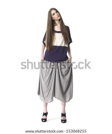 Full length young woman standing on white background - stock photo