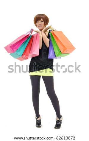 full length young woman with lots of shopping bags walking on white background - stock photo
