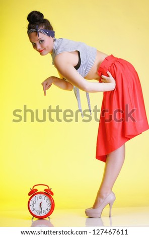 Full length young woman with red clock yellow background. Time management concept - stock photo