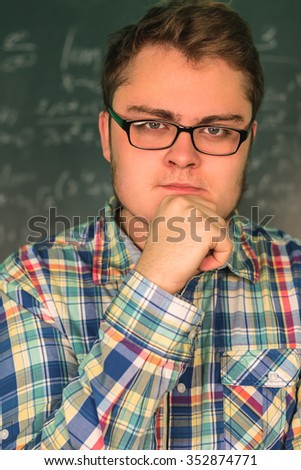Full man in glasses close-up on a background blackboard with mathematical solutions of higher mathematics with mood, determined look. The man's face, looking at the camera. figures, numeral, number - stock photo