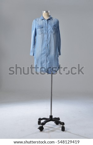 Full mannequin in female long blue shirt clothes isolated on gray background