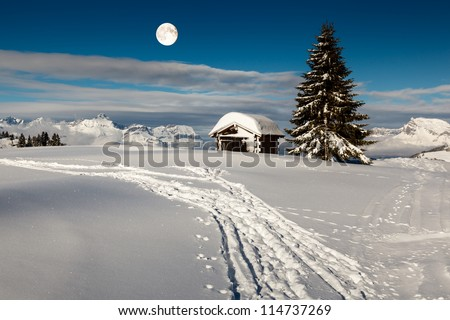 Full Moon above Small Hut and Fir Tree on the Top of the Mountain in Megeve, French Alps - stock photo