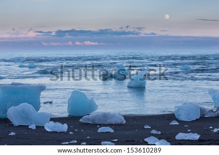 Full Moon and blue icebergs floating near Jokulsarlon glacial lagoon beach at sunset, Iceland