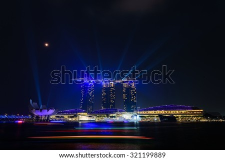 Full moon and lighting show over Singapore landmarks and tourist attraction. Mid-autumn is a big holiday in Asia. People celebrate full moon with moon cake, street lion dancing and flying lantern - stock photo