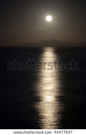 Full moon at night over Tiran island in the Red sea - stock photo