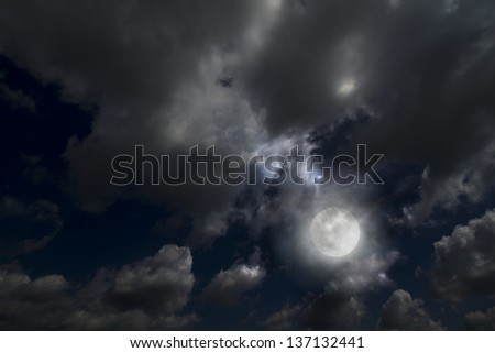 Full moon between dramatic clouds