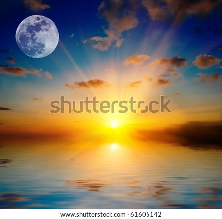 full moon by a majestic sunset above a lake - stock photo
