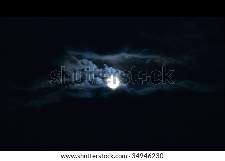 Full Moon emerging from clouds. - stock photo