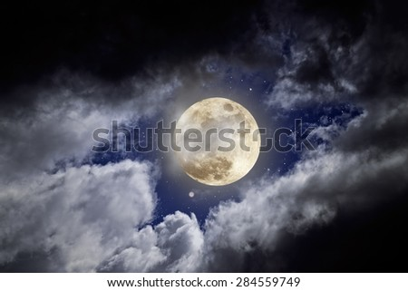 Full moon in a cloudy night with stars - stock photo