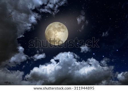 Full moon in a starry night with some clouds - stock photo