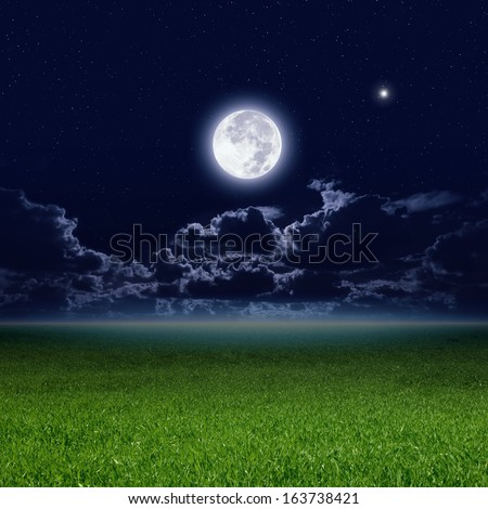 Full moon in dark night sky with stars and clouds, green grass field. Elements of this image furnished by NASA - stock photo