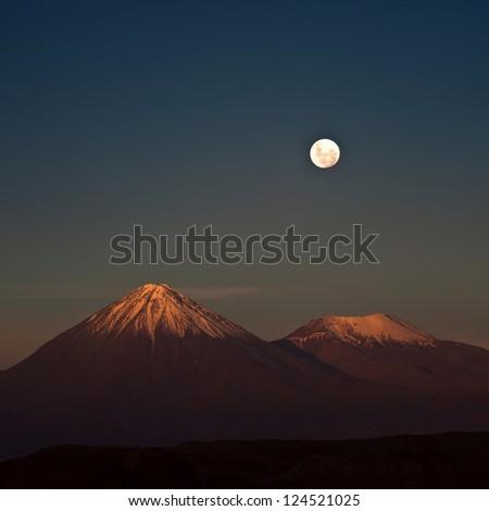 Full-moon in the Moon Valley. Volcanoes Licancabur and Juriques, west of San Pedro de Atacama, Chile in the Cordillera de la Sal, in the Atacama desert of Chile - stock photo