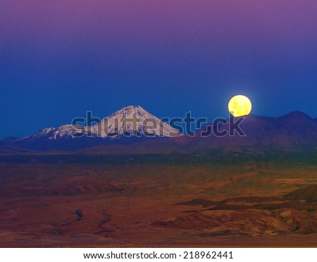 Full-moon in the Moon Valley. Volcanoes Licancabur and Juriques, west of San Pedro de Atacama, Chile in the Cordillera de la Sal, in the Atacama desert of Chile - stock photo