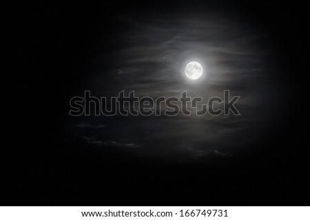 full moon in translucent clouds shining in the darkness - stock photo