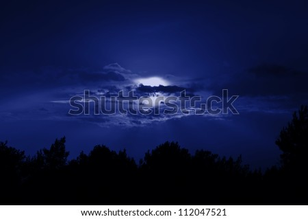 Full moon obscured by clouds. Night sky moonlight nature background. - stock photo