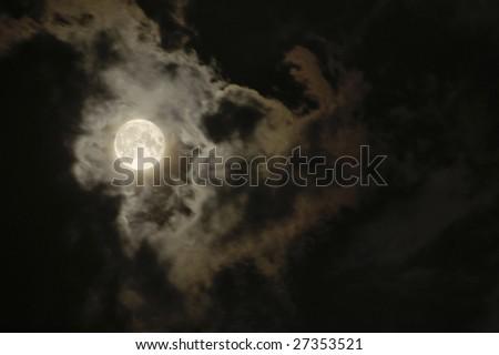 Full moon on a dark cloudy sky - stock photo