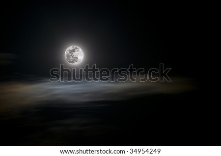 Full moon on a hazy night over passing clouds with copy space - stock photo