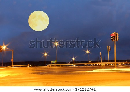 Full Moon over an empty highway crossing at night. - stock photo