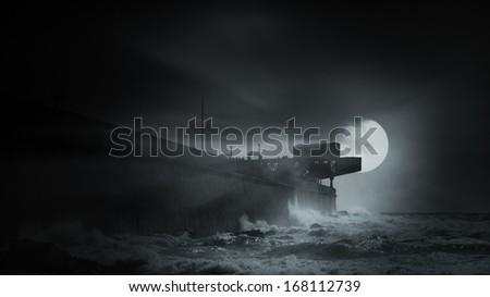 Full moon over an old harbor wall in a foggy and overcast night - stock photo