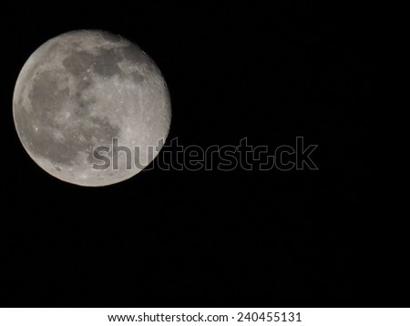 Full moon over dark black sky at night seen with a telescope from northern hemisphere