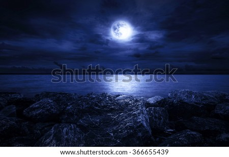 Full moon over the ocean with clouds and rocks - stock photo