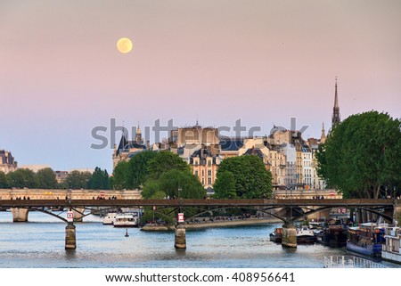 Full moon rise at a pink twilight over the Seine in Paris, France - stock photo