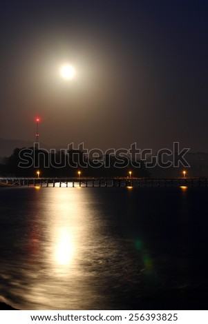 Full moon rise over the Goleta pier. - stock photo