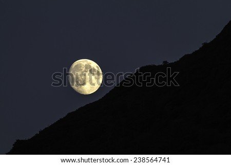 Full moon rising over a silhouetted ridge on a clear night - stock photo
