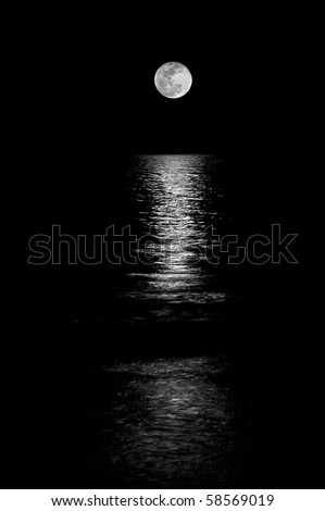 Full moon setting on the horizon in the ocean with reflection shining through. Black and White. - stock photo
