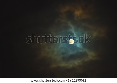 Full moon shines through dramatic sky surrounded clouds - stock photo