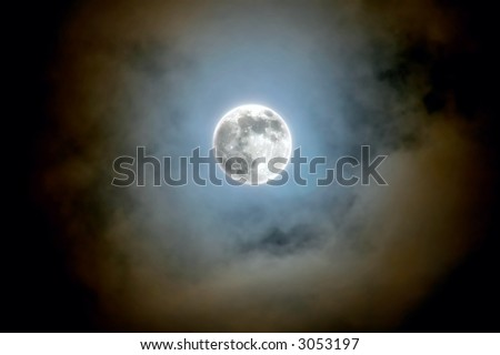 full moon shines through the clouds
