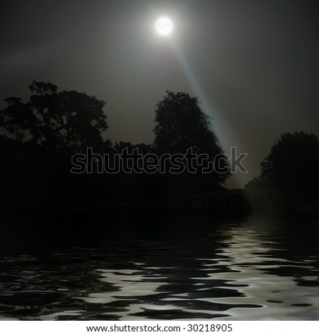 Full Moon shining above tree silhouettes and water.