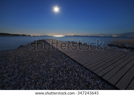 full moon, which is mirrored in the lake - stock photo