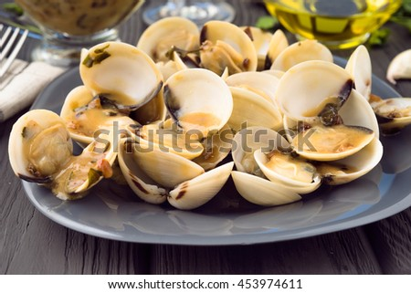 full of clams in sauce dish over black wood gray - stock photo
