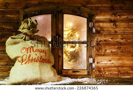 Full of Gifts Santa Sack at Vintage Wooden Window Pane During Christmas. - stock photo
