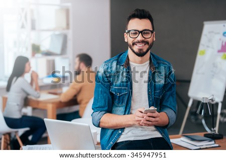 Full of new great ideas. Confident young man holding smart phone and looking at camera with smile while his colleagues working in the background - stock photo
