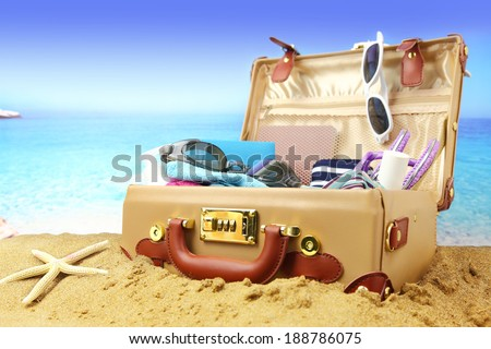 Full open suitcase on tropical beach background  - stock photo