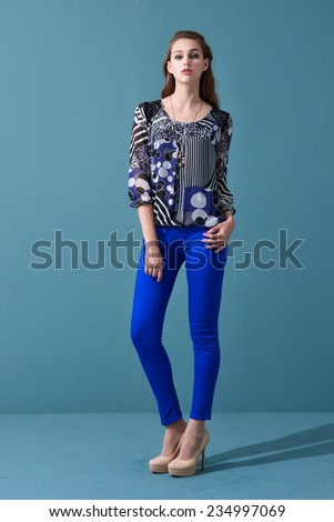 Full picture of casual young woman in blue jeans posing on light background - stock photo