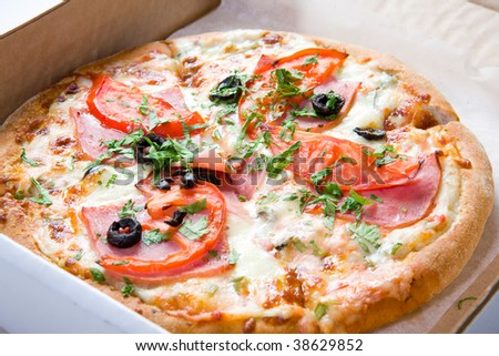 Full pizza in box on white ground - stock photo