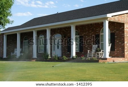 Full porch on a new brick house with white columns, porch furniture, flower beds, lush green grass and water sprinklers turned on.