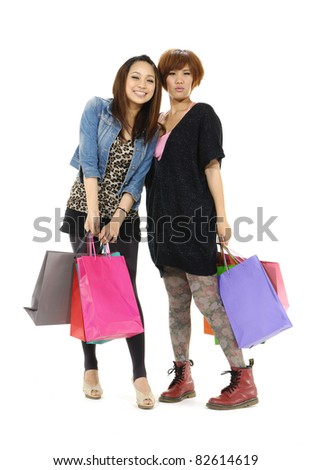Full portrait of Asian girls standing with shopping bags - stock photo