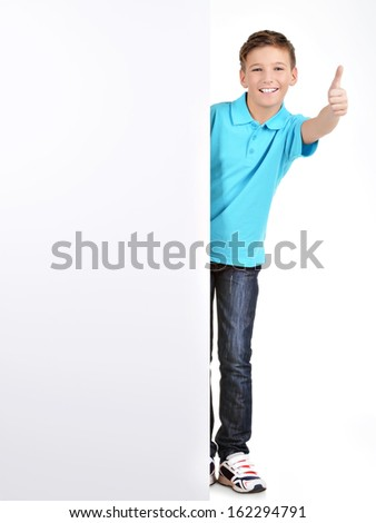 Full portrait of  cheerful boy looks out from the  white banner with thumbs up gesture- isolated on white background - stock photo
