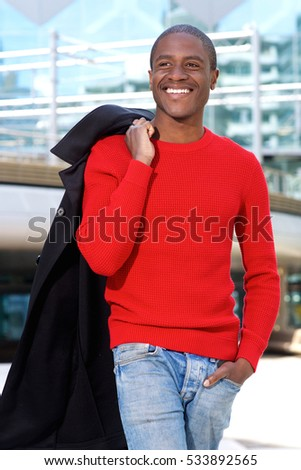 Full portrait of happy young african american man standing with jacket over shoulder