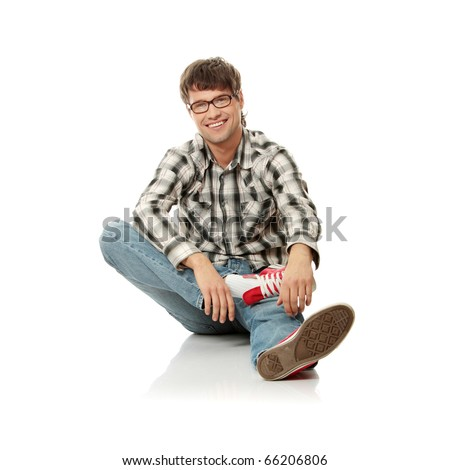 Full portrait of smiling handsome man sitting on the flor - stock photo